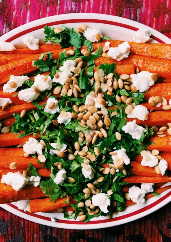 Up close shot of Honey Sriracha Roasted Carrots with Goat Cheese, Pepitas + Cilantro