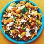 Turmeric Roasted Cauliflower with Honey Harissa Butternut Squash + Crispy Chickpeas with Fresh Herbs + Feta on a blue plate with a yellow background