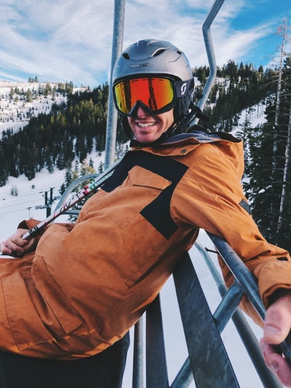 Jeremy Johnston in an orange Dakine Snow Jacket on the ski lift in Deer Valley Utah