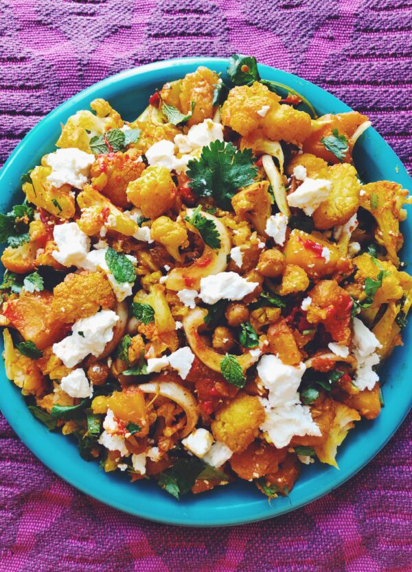 Turmeric Roasted Cauliflower with Honey Harissa Butternut Squash + Crispy Chickpeas with Fresh Herbs + Feta on a blue plate with purple background