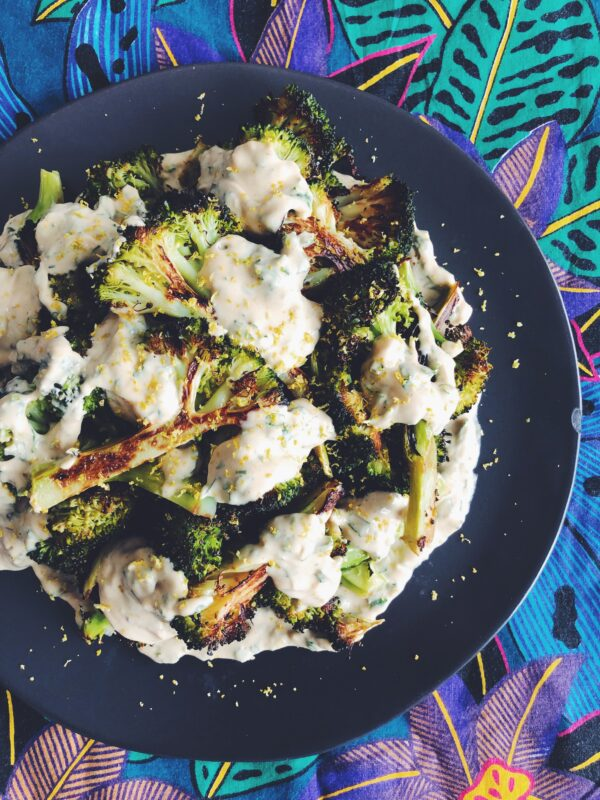 Roasted Broccoli with Lemon Herb + Garlic Tahini Sauce on a black plate