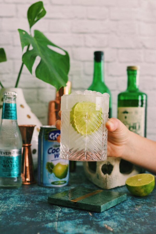 a hand holding a mezcal cocktail in a clear glass with a big lime wedge in it. The background has bottles and a turtle skull with fresh palm leaves