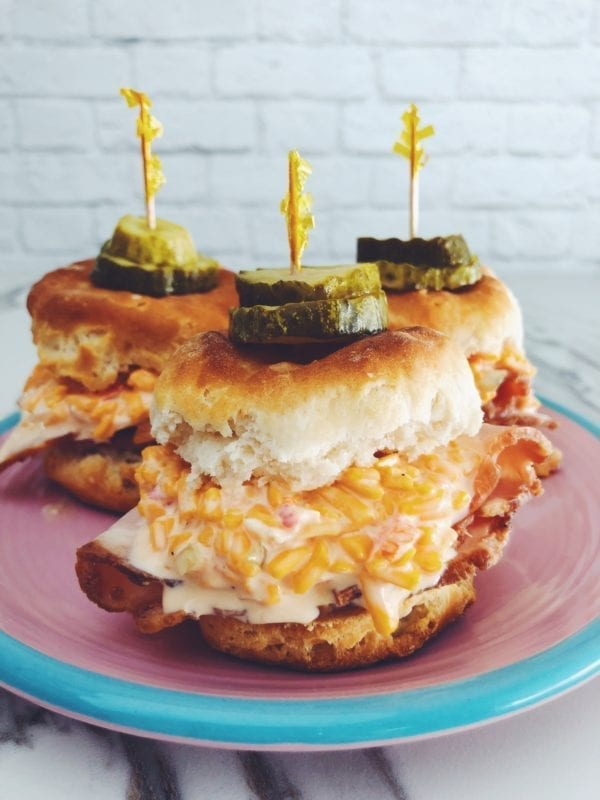 three pimento cheese biscuit sliders on a pink and blue plate with a white background