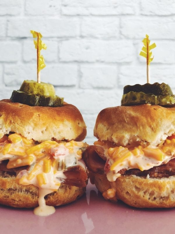 two pimento cheese biscuit sliders on a pink and blue plate with a white background