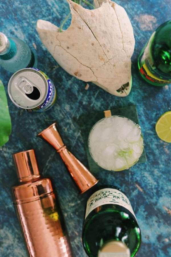overhead shot of margarita ingredients with bronze shakers