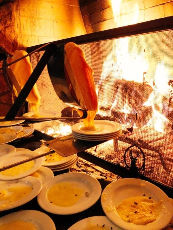 Hot melty raclette cheese melting over a fireplace at Fireside Dining, Deer Valley Utah