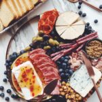 a wooden cheese plate full of meats, pickles, and fresh fruit on a white marble counter top