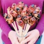 two hands holding a bacon wrapped date bouquet with a purple shirt in the background