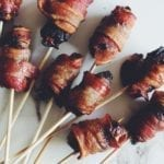 bacon wrapped dates stuffed with blue cheese with a skewer through them on a white countertop
