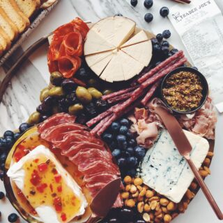 a wooden cheese plate full of meats, pickles, and fresh fruit on a white marble counter top with a receipt in a corner.