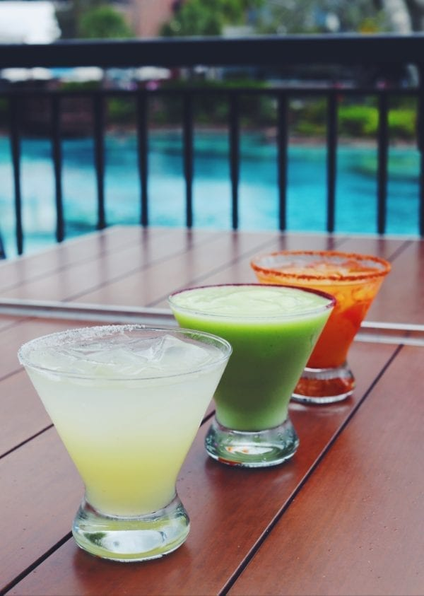 three different colored margaritas in front of disney's springs