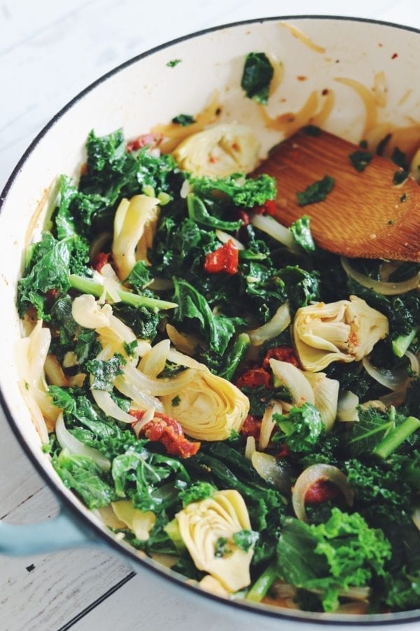bright green kale, sun dried tomatoes, and artichokes in a pan with a wooden spoon and a white background