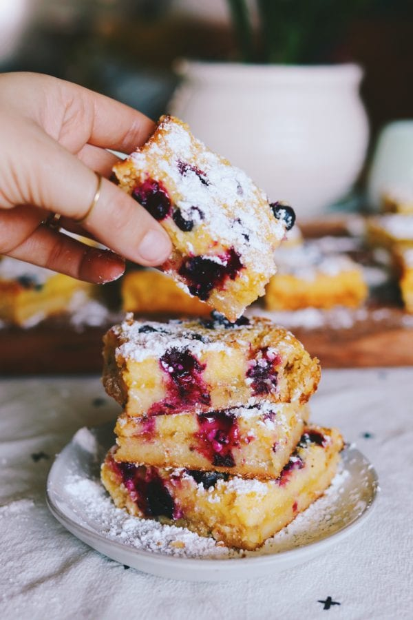 stacked blueberry lemon bars with a hand reaching in