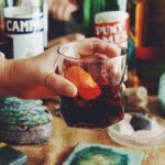 a hand holding a clear glass full of redish brown liquor with an orange slice in it - various bottles in the background