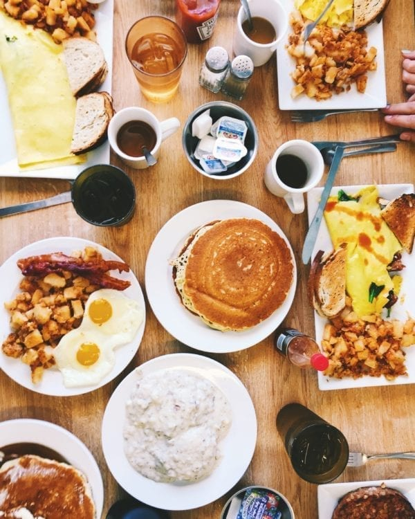 an overhead shot of a breakfast table with pancakes, eggs, bacon, potatoes, and coffee