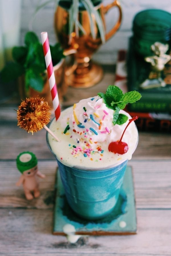 a shiny aqua cup filled with a green milkshake with rainbow sprinkles, whipped cream and a cherry on top