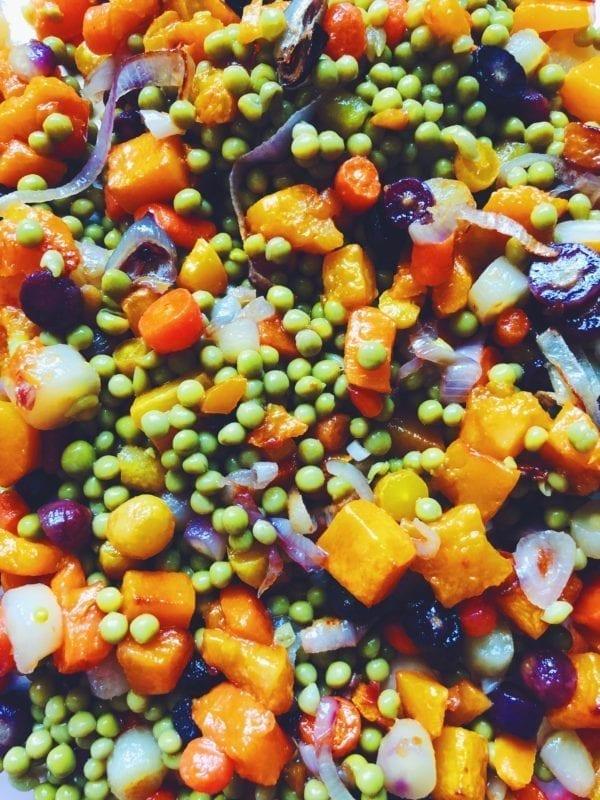 peas, carrots, squash and shallots on a baking dish