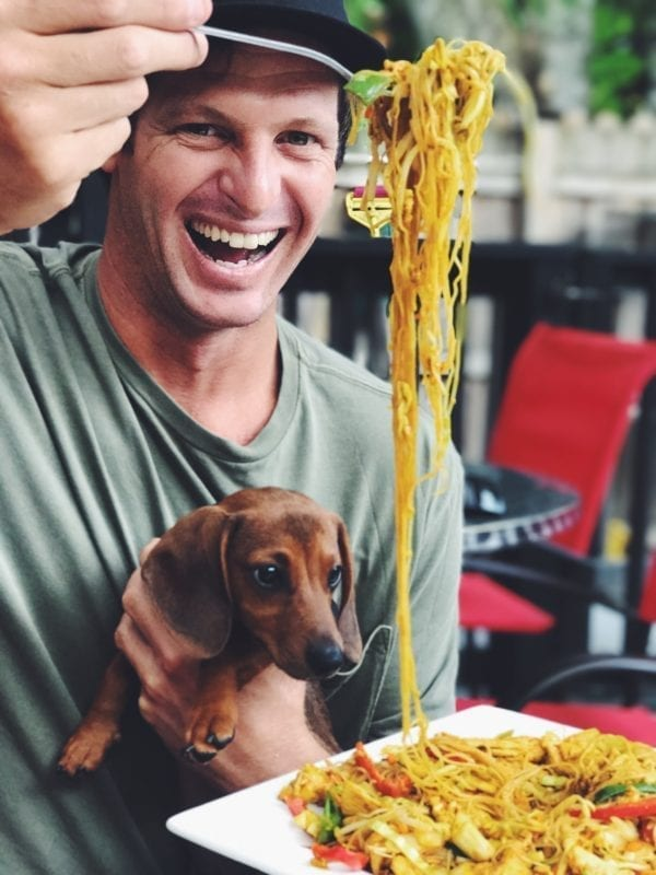 a man holding up chopsticks with noodles sprawling down with a dog trying to get a bite