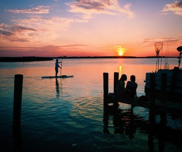 a paddle boarder paddling across the water with a colorful sunset in the background