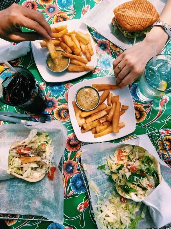 yuca fries and sandwiches spread across a colorful table with hands reaching in
