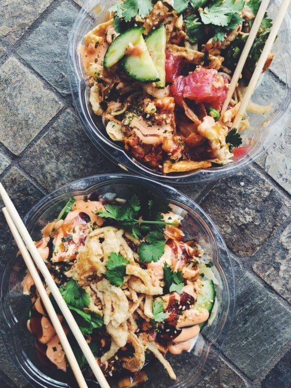 two colorful poke bowls with chopsticks on a wooden table