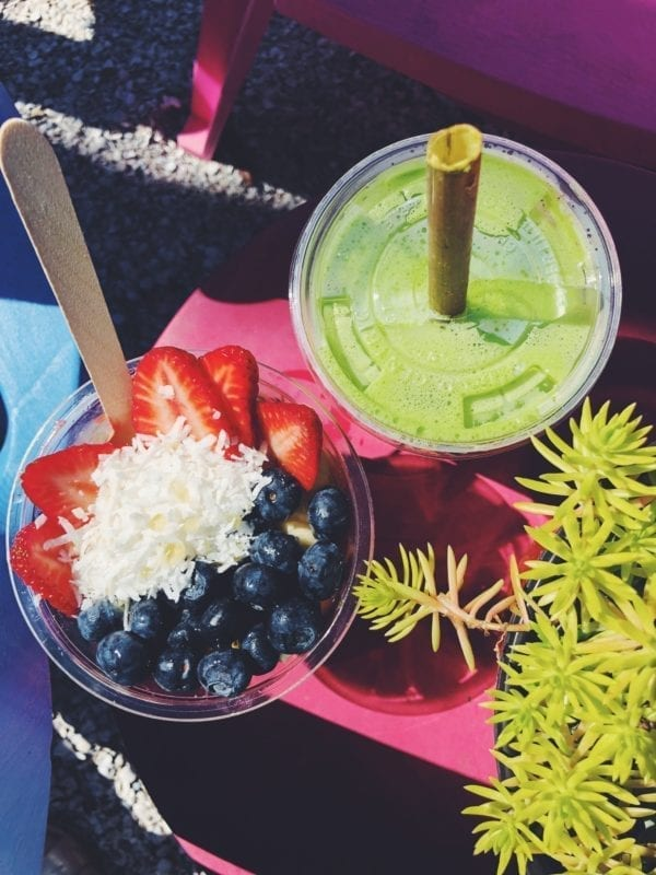 strawberry blueberrie and coconuts in a bowl with a bright green juice on a pink table