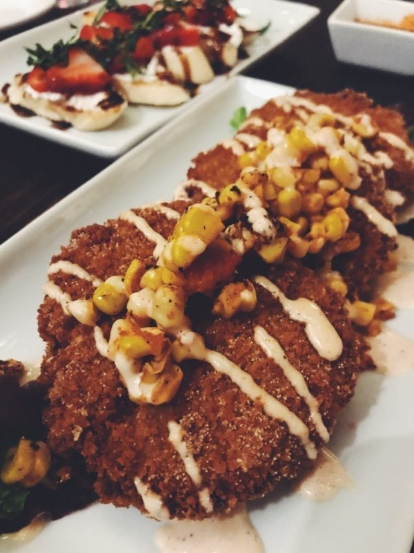 fried green tomatoes with a light pink drizzle and yellow corn on top