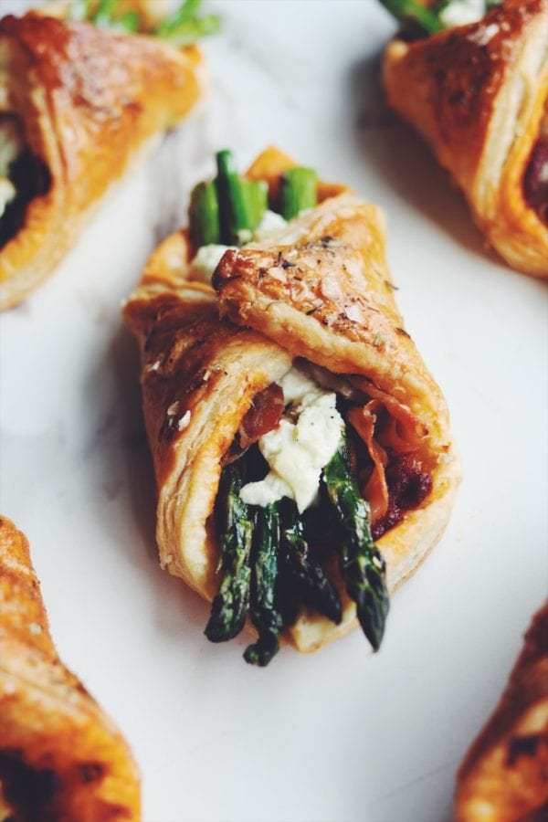 asparagus wrapped in puff pastry on a white counter top