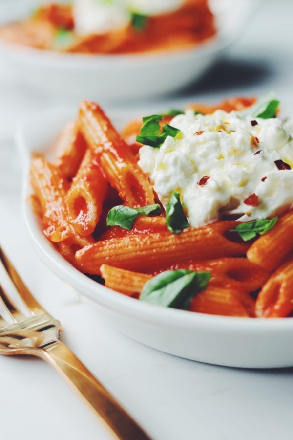 a bowl of penne pomodoro with burrata and basil on top
