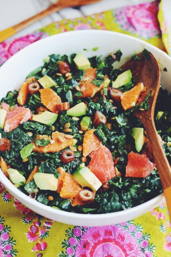 kale salad with chunks of citrus in a white bowl