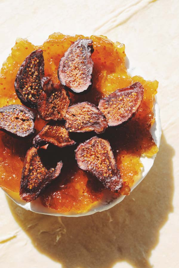 fig jam and dried figs on top of brie