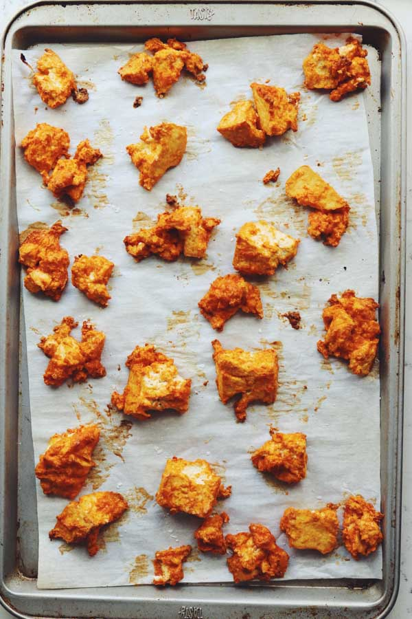 These crispy baked buffalo tofu wings are super easy to make and they taste SO GOOD! They're made by tearing pressed tofu into nuggets and tossing them in a slurry of buffalo sauce, parmesan cheese and cornstarch. After baking, they turn into crunchy, spicy and savory tofu buffalo wings! I like to serve them loaded with blue cheese, ranch and scallions but you could totally eat them plain, too!