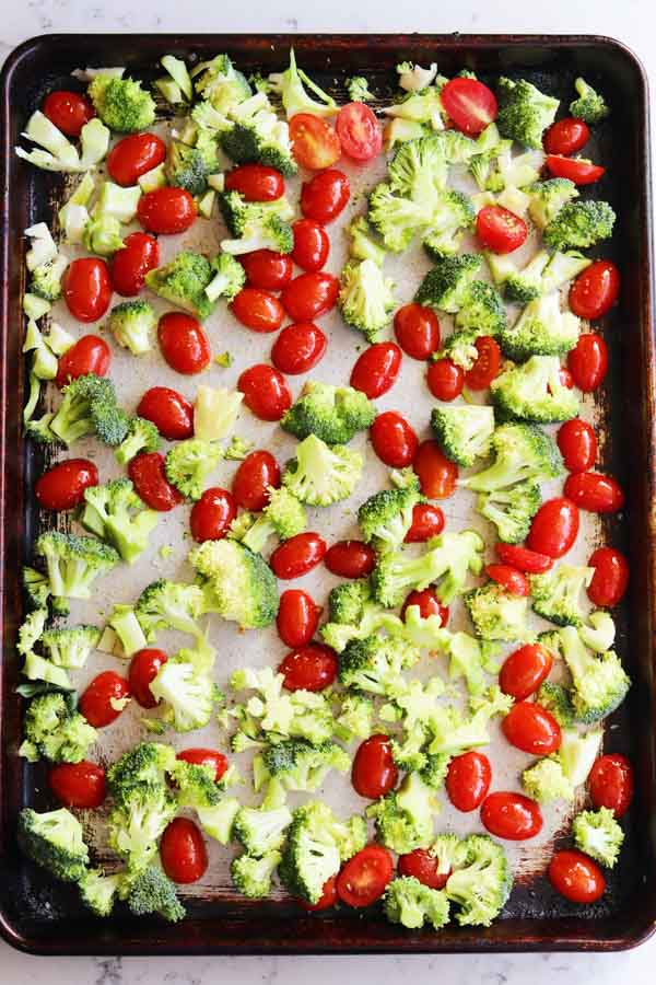 tomatoes and broccoli on a baking sheet